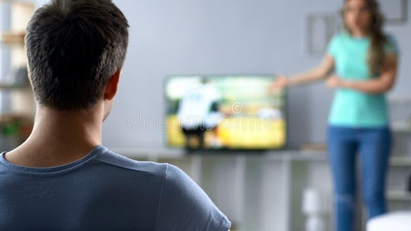 Dziewczyna nerwowo krzyczy przy facetem, zakazuje on oglądać tv sportów rywalizację zdjęcia royalty free