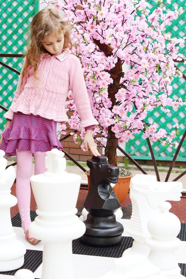 Dziewczyna obok sztucznego czereśniowego okwitnięcia dotyka dużych szachowych kawałki fotografia royalty free