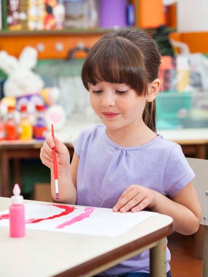 Dziewczyna obraz Przy biurkiem W sztuki klasie obrazy royalty free