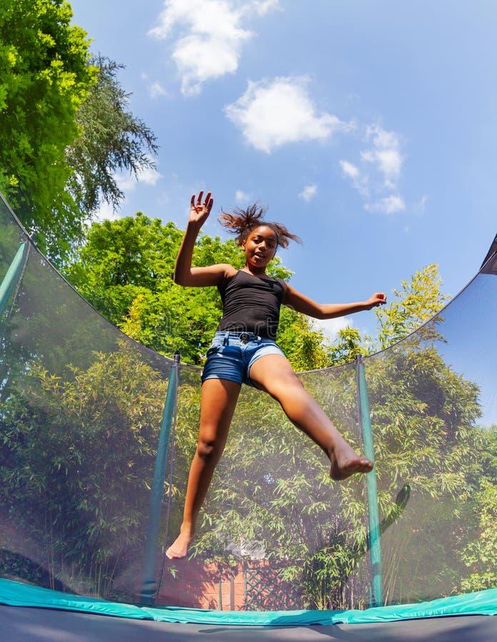 Dziewczyna odbija się up na podwórka trampoline w lecie obraz stock