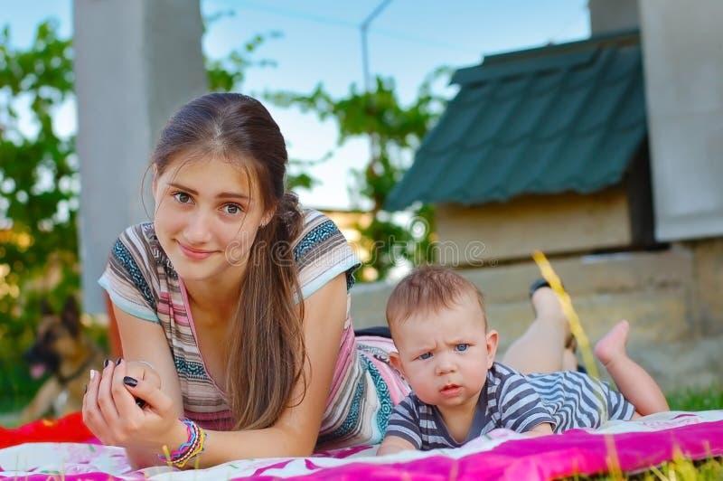 Dziewczyna odpoczynek z jej bratem na różowej koc obraz stock