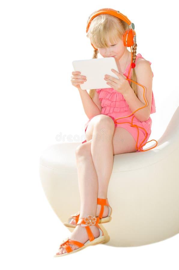 Dziewczyna ogląda wideo w hełmofonach z pastylka pecetem ja obraz stock