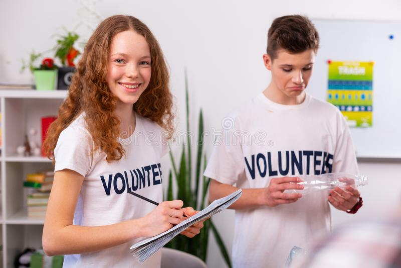 Dziewczyna ono uśmiecha się podczas gdy sortujący odpady z jej najlepszym przyjacielem w szkole fotografia royalty free