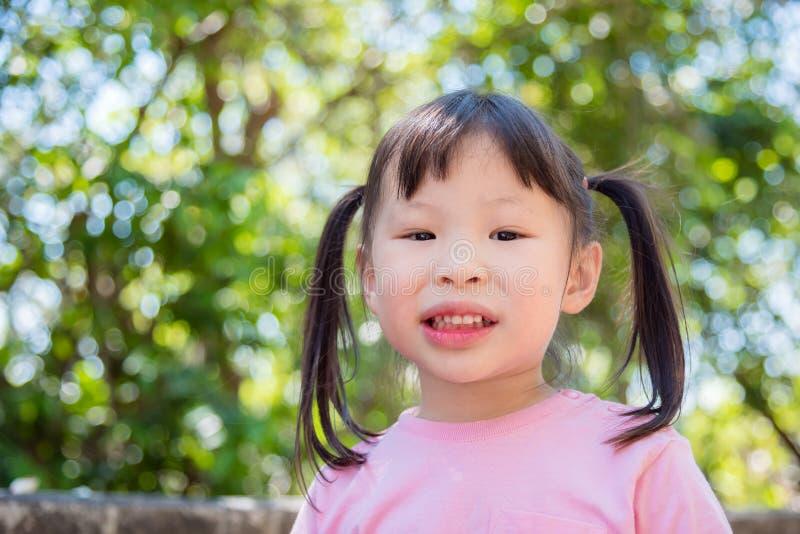 Dziewczyna ono uśmiecha się podczas gdy stojący w podwórku obrazy stock