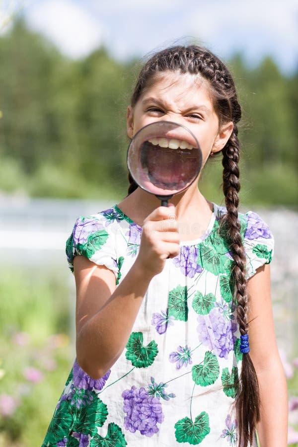 Dziewczyna ono uśmiecha się przez powiększać - szkło zdjęcie stock