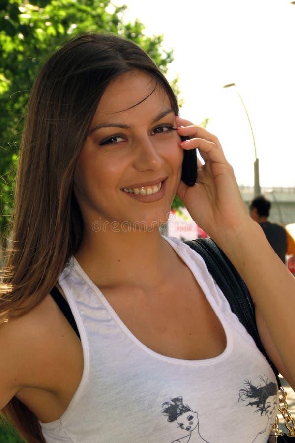 Dziewczyna ono uśmiecha się z mobilny opowiadać obrazy royalty free