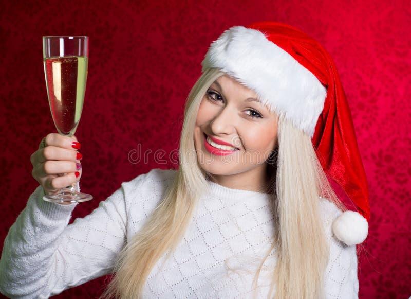Dziewczyna ono uśmiecha się z szkłem czempion w Santa kapeluszu w białym pulowerze zdjęcia stock