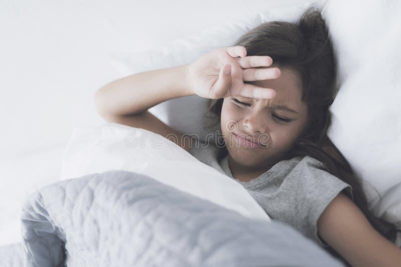 Dziewczyna ono zakrywa z ręką od jaskrawego światła lying on the beach w białym łóżku pod szarą koc obrazy royalty free