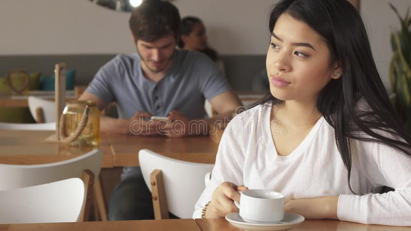 Dziewczyna opiera jej podbródek na jej ręce przy kawiarnią fotografia royalty free