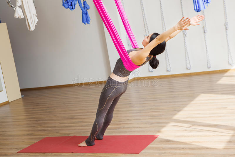 Dziewczyna opiera z powrotem z hamakiem robi powietrznym joga ćwiczeniom fotografia stock