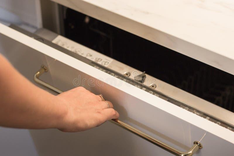 Dziewczyna otwiera dekiel zmywarka do naczyń dla myć naczynia zdjęcia royalty free