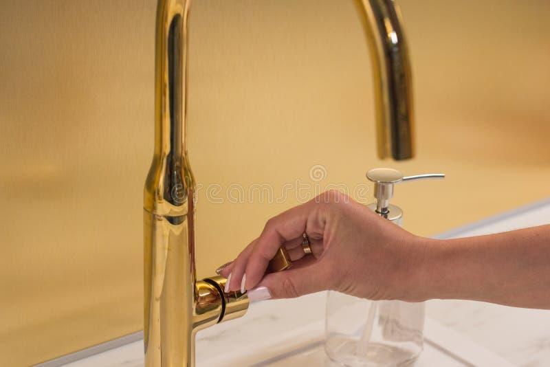 Dziewczyna otwiera faucet dla myć ręki zdjęcie royalty free