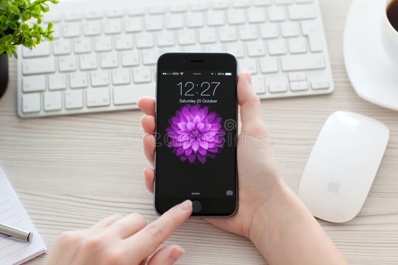 Dziewczyna otwiera iPhone 6 Astronautycznych szarość nad stołem obraz stock