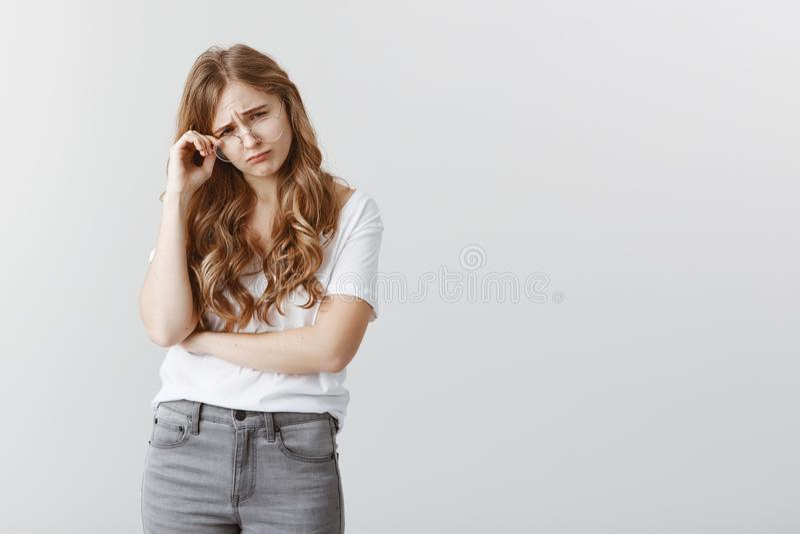 Dziewczyna płacze od przeciwności Wzburzona ponura atrakcyjna dziewczyna z blondynem, brać daleko szkło, marszczy brwi i obraz royalty free