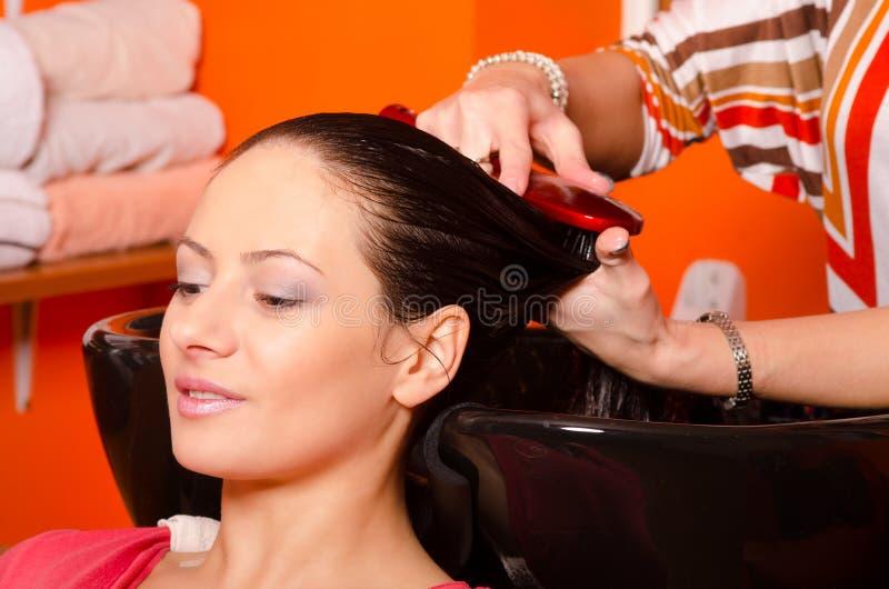 Dziewczyna płuczkowy włosy w fryzjerstwo salonie obrazy royalty free