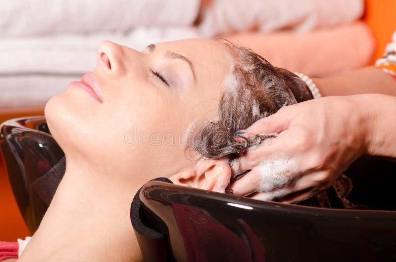 Dziewczyna płuczkowy włosy w fryzjerstwo salonie obraz stock