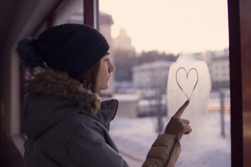 Dziewczyna palcowy obraz na szklanym sercu zdjęcia stock