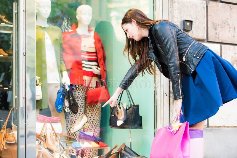 Dziewczyna patrzeje i wskazuje nowe wykazywać tendencję torby i buty co chce obrazy stock