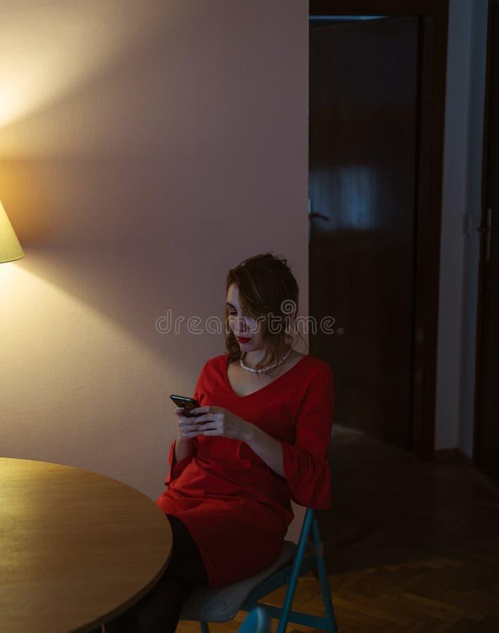 Dziewczyna patrzeje jej telefon w czerwieni sukni fotografia royalty free