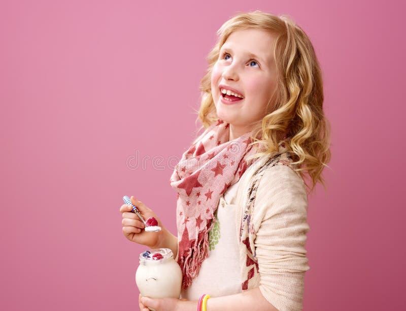 Dziewczyna patrzeje kopii przestrzeń i trzyma rolnego organicznie jogurt fotografia royalty free