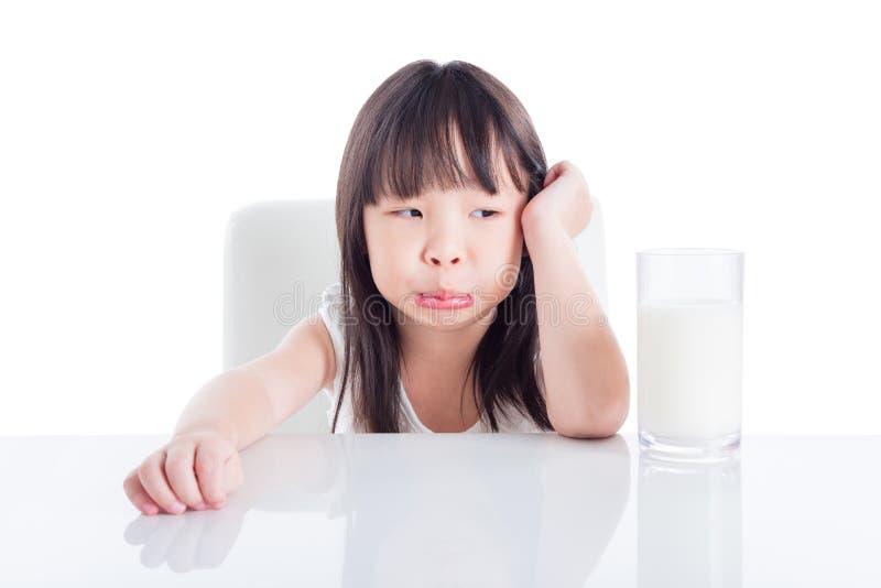 Dziewczyna patrzeje szkło mleko z nieszczęśliwą twarzą obraz royalty free