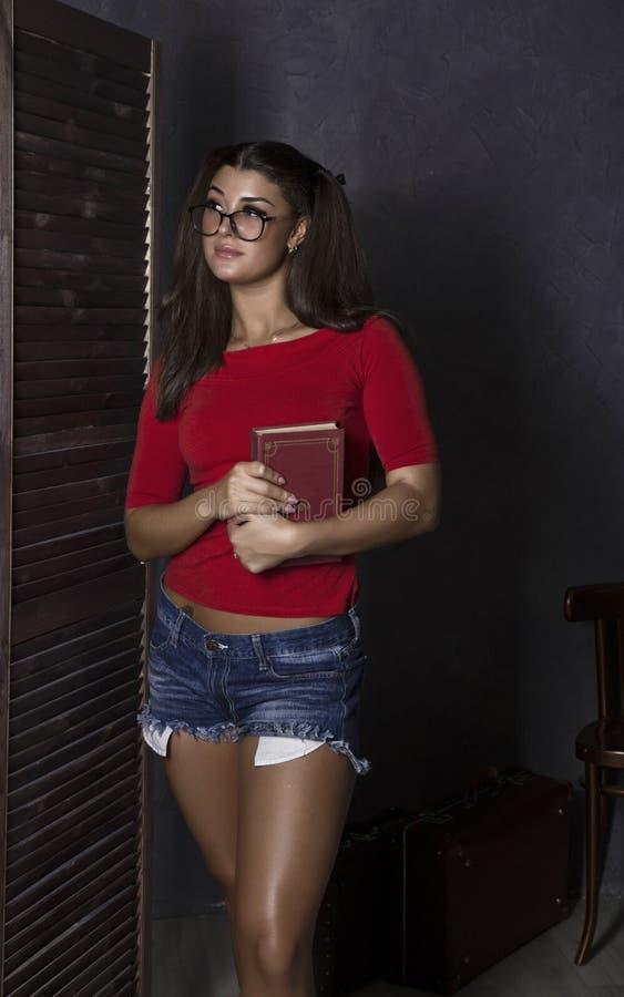 dziewczyna piękny książkowy uczeń młoda kobieta w czerwonym wierzchołku i drelichu zwiera z szkłami zdjęcia stock