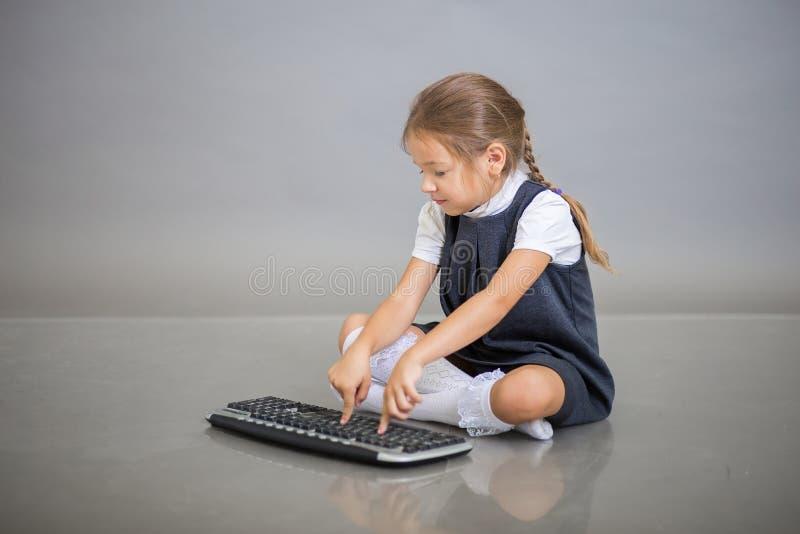 Dziewczyna pierwszy równiarka w mundurku szkolnym siedzi na szarym tle i pracuje na klawiaturze od komputeru obraz stock