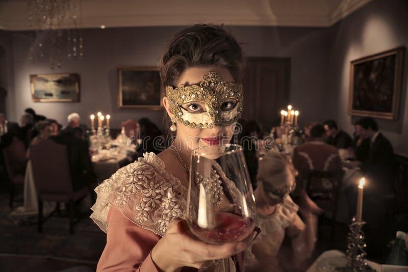 Dziewczyna pije przy maskaradowym przyjęciem obrazy stock