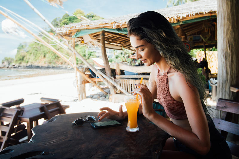 Dziewczyna pije sok i sprawdza telefon kawiarni na wakacje z widokiem morza i plaży zdjęcie stock