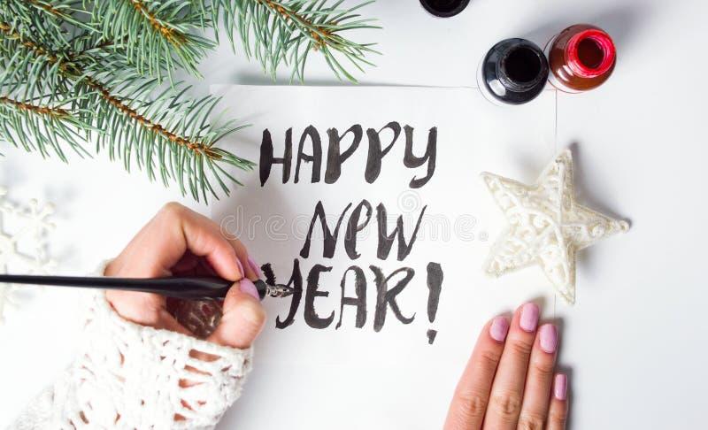 Dziewczyna pisze Szczęśliwej nowy rok kaligrafii karcie obraz stock