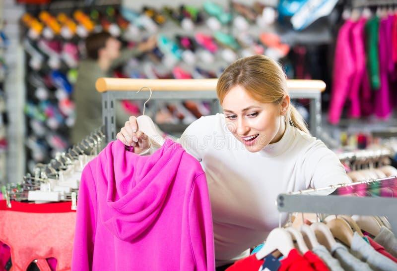 Dziewczyna podnosi kardigan w sklepie zdjęcia royalty free