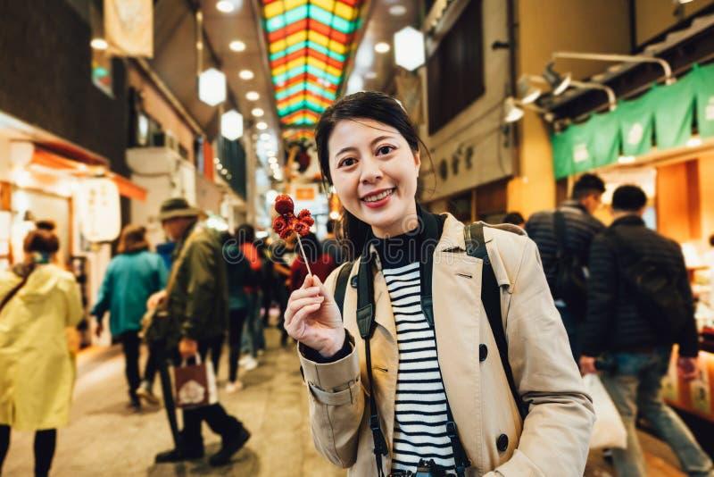Dziewczyna podróżnik próbuje japońskiego przekąski ulicy jedzenie zdjęcie royalty free