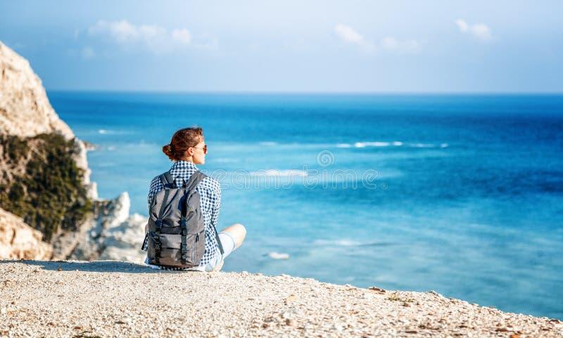 Dziewczyna podróżnik siedzi na skale i podziwia błękitnego bezbrzeżnego se obraz royalty free