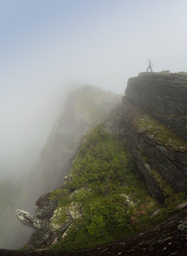 Dziewczyna podróżnik wspinał się na wierzchołku góra, obsiadanie i patrzeć na, zmierzchu i mgle fotografia stock