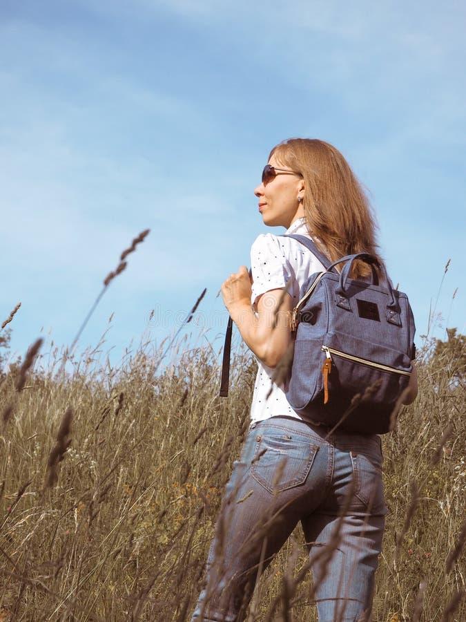 Dziewczyna podróżnik wycieczkuje z plecakiem przy Alpejskimi łąkami Podróż stylu życia pojęcia przygody wakacje plenerowi zdjęcia royalty free