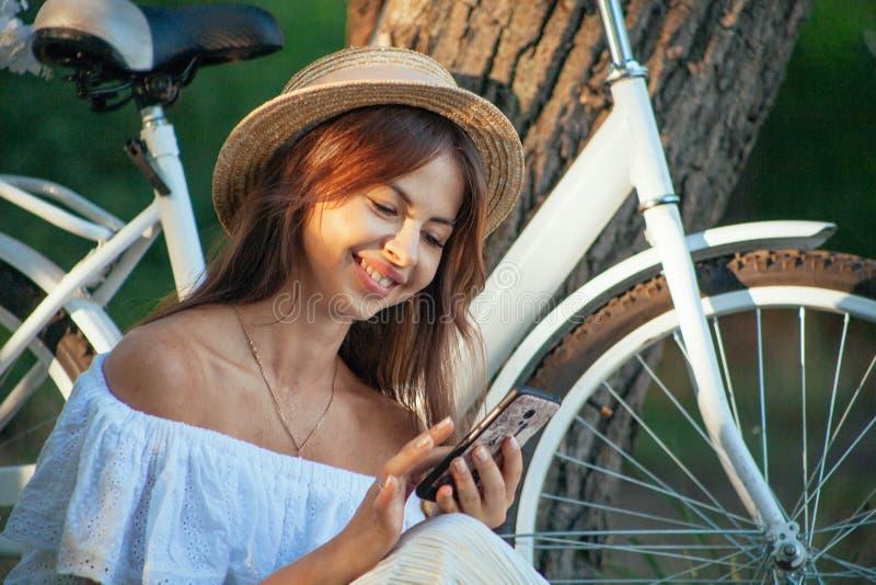 Dziewczyna podrzuca przez fotografii w telefonie i ono uśmiecha się obraz stock