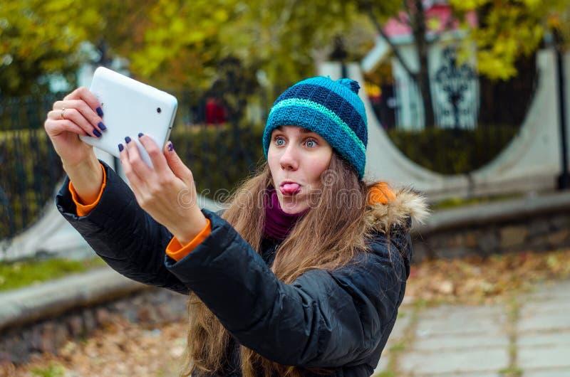 Dziewczyna pokazuje języka dla fotografii na pastylce obrazy stock