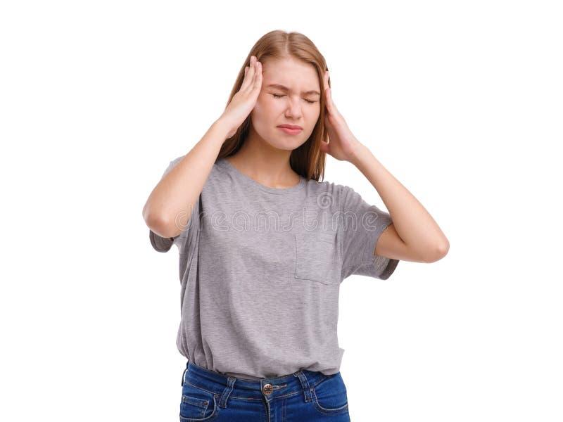 Dziewczyna pokazuje migreny mieniu ręki za głową Odizolowywający na bielu obraz stock