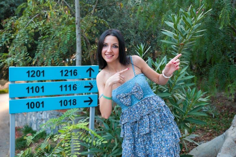 Dziewczyna pokazuje na drogowym znaku, wskazuje kierunek ścieżka zdjęcie royalty free