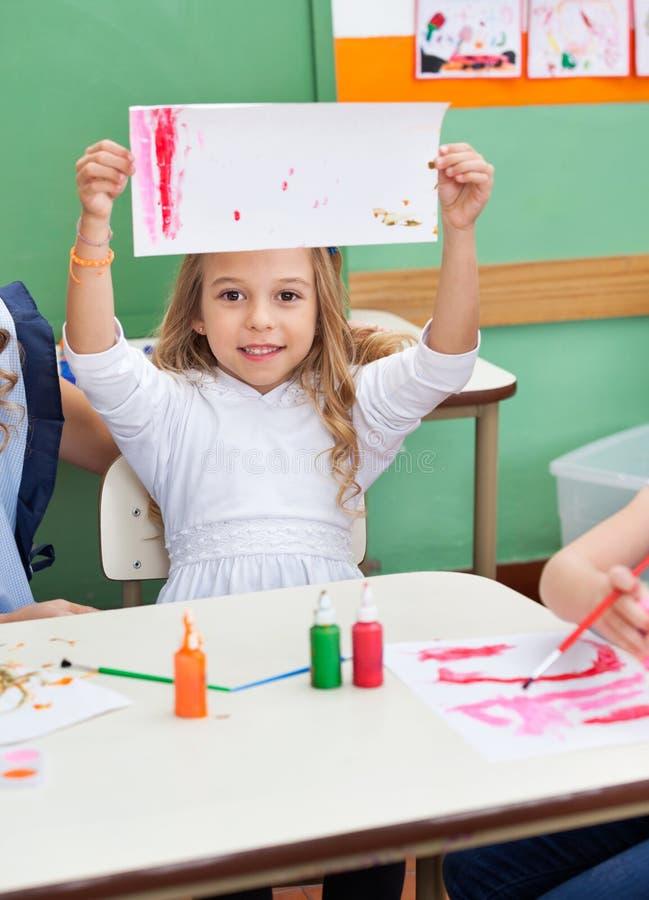 Dziewczyna Pokazuje obraz Przy sala lekcyjnej biurkiem zdjęcia royalty free