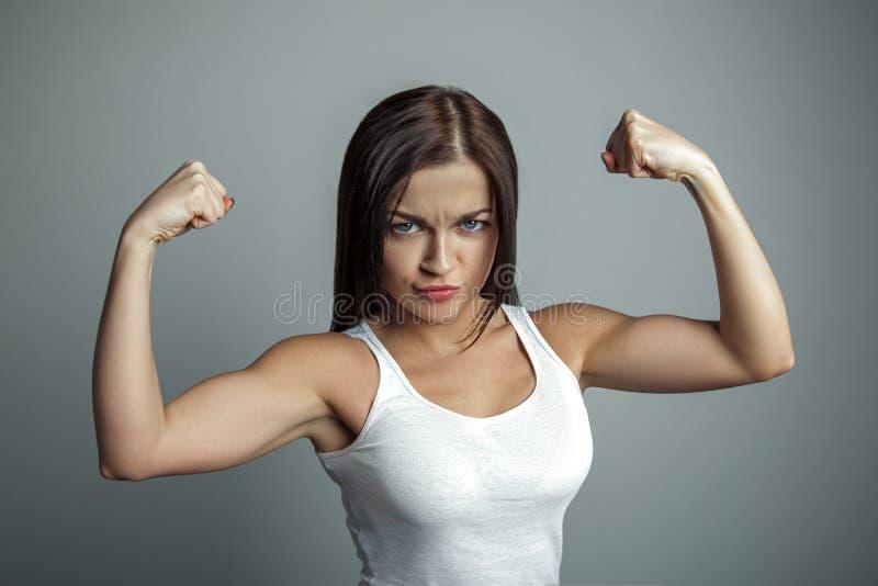 Dziewczyna pokazuje ona bicepsy zdjęcia stock