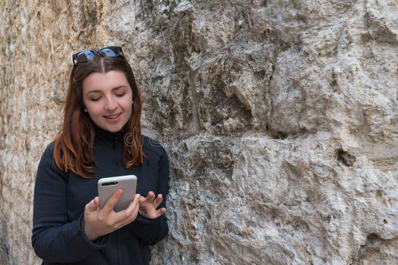 dziewczyna polega na kamiennej ścianie z cegieł antyczna średniowieczna ulica Rudzielec pisać na maszynie smartphone młoda kobiet obrazy stock