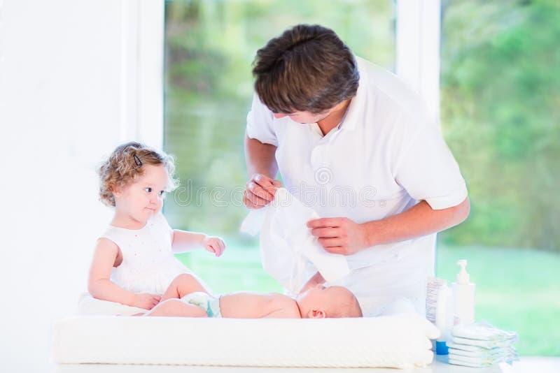 Dziewczyna pomaga jej ojca wybierać strój dla jej brata obrazy stock