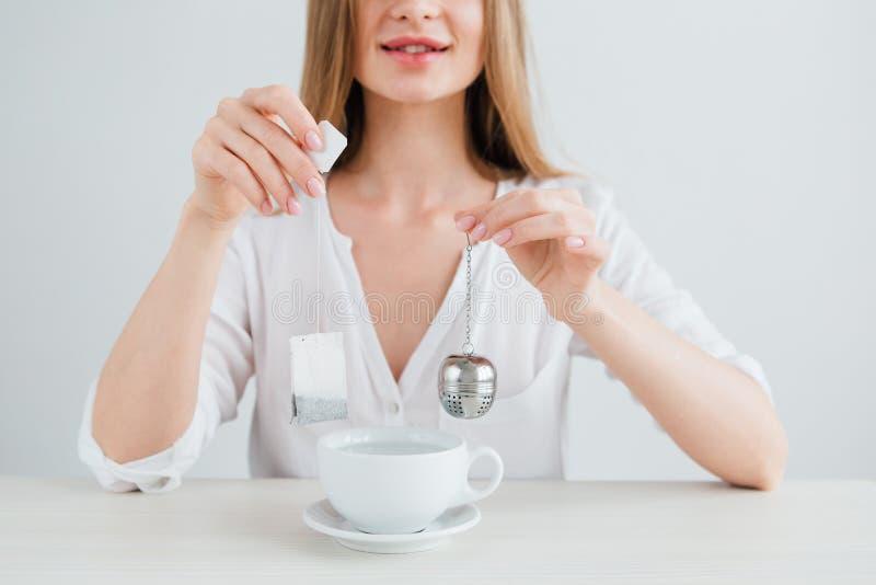 Dziewczyna porównuje pożytecznie reusable metalu herbacianego durszlaka z szkodliwą herbacianą torbą obraz stock