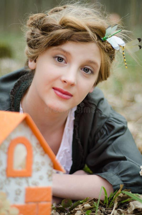 Dziewczyna pozuje blisko rocznik lali domu obrazy stock