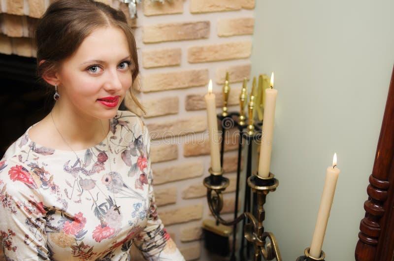 Dziewczyna pozuje w pięknym smokingowym obsiadaniu blisko świecznika z świeczkami zdjęcia stock