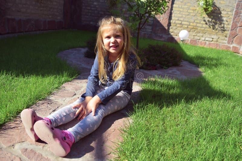 Dziewczyna pozuje z śliczną twarzą Mieć zabawę na ogródzie Szczęśliwa berbeć dziewczyna bawić się outside obrazy stock