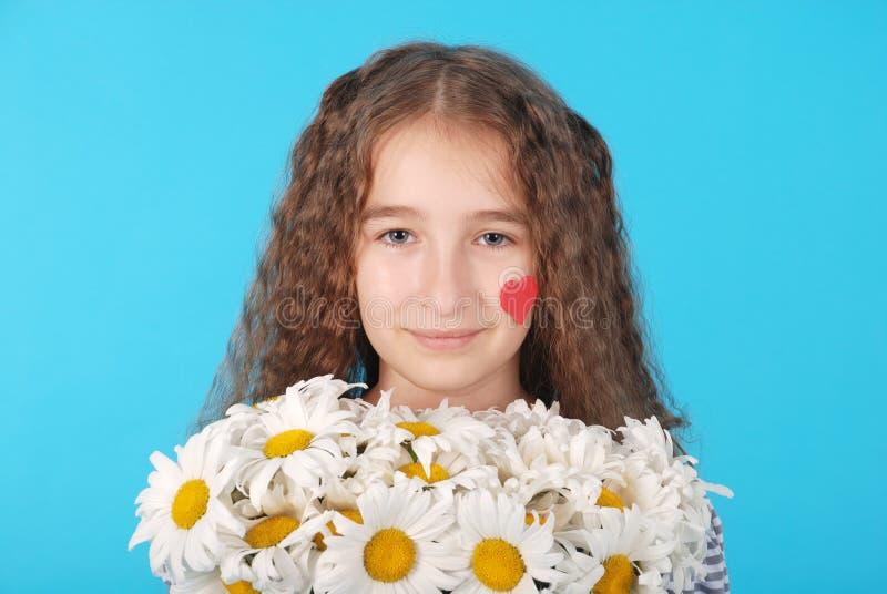 Dziewczyna pozuje z stokrotkami zdjęcie stock