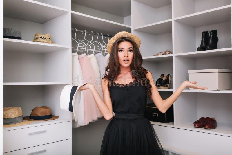 Dziewczyna próbuje wybierać kapelusz w garderobie zdjęcia stock