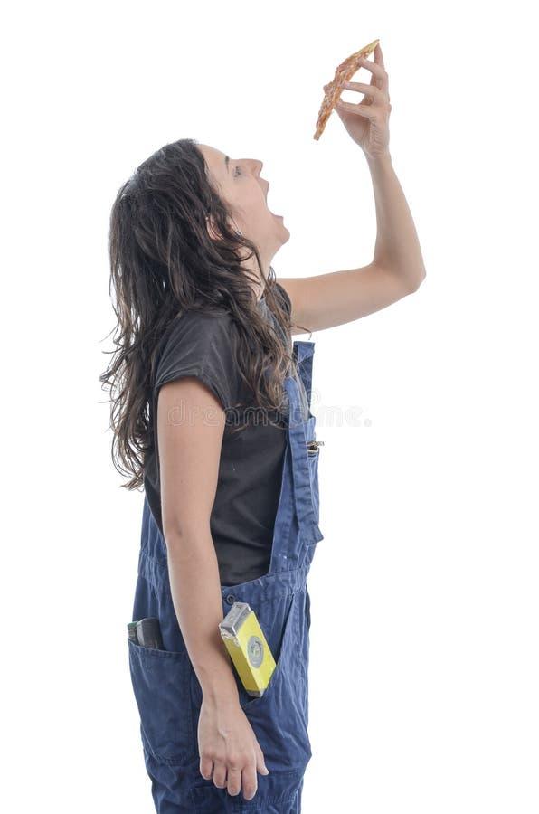 Dziewczyna pracownik je pizzę zdjęcie royalty free